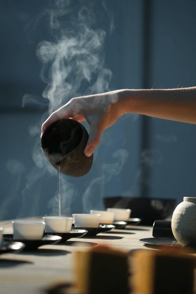 Main versant du thé dans des tasses